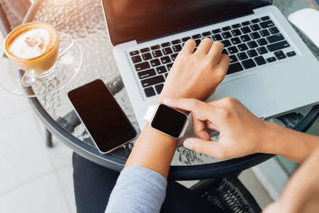 Photo pour woman using smart watch in coffee shop, modern city lifestyle - image libre de droit