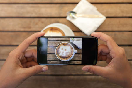 Photo pour close-up hand holding phone taking coffee photo on table - image libre de droit