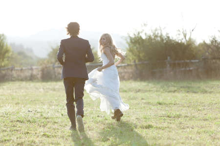 Foto de Married couple running in a field, having fun and smiling. She is looking back. - Imagen libre de derechos