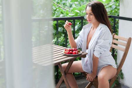 Foto für Young woman having a relaxing time enjoying fresh strawberries. - Lizenzfreies Bild