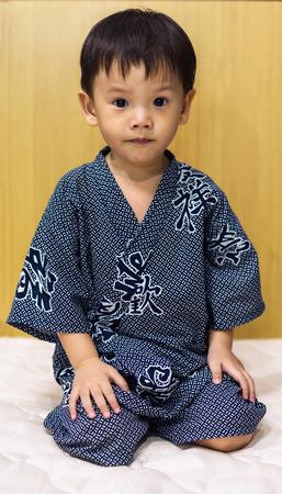 Cute asian boy in kimono dress sitting on white sheet