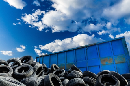 Recycling business with metal container and car tires over blue sky Ecology and recycle industry, saving nature and environment