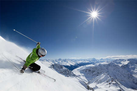 Photo pour Female skier on downhill race with sun and mountain view. - image libre de droit