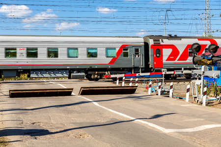 Foto per Samara, Russia - September 23, 2018: Traffic light and road sign on the railway crossing during the passage of a train with wagons - Immagine Royalty Free