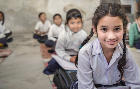 Foto de Girl sitting on the floor of her government primary school in uniform along with some of her class mates sitting behind her. Selective focus, shallow depth of field. - Imagen libre de derechos