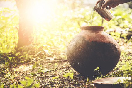 Photo for Man drinking water from clay pot stored below the tree during summer - Royalty Free Image