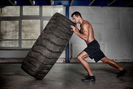 Photo pour crossfit training - man flipping tire - image libre de droit