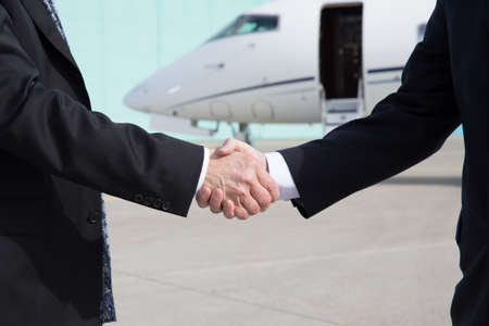 Foto per Businessmen shake hands in front of a corporate jet - Immagine Royalty Free