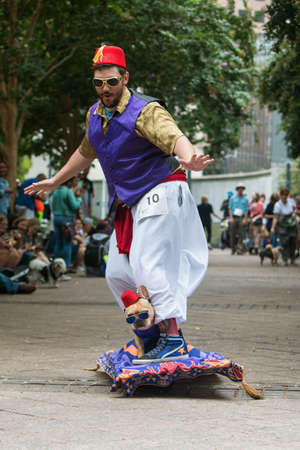 Photo pour Atlanta, GA, USA - August 18, 2018:  A costumed dog rides with its owner on a motorized skateboard made to look like Aladdin's flying carpet at Doggy Con, a dog costume event on August 18, 2018 in Atlanta, GA. - image libre de droit