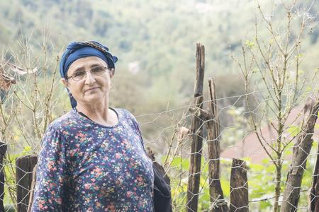 Photo pour Portrait of an elderly woman with eyeglass in front of hedge - image libre de droit