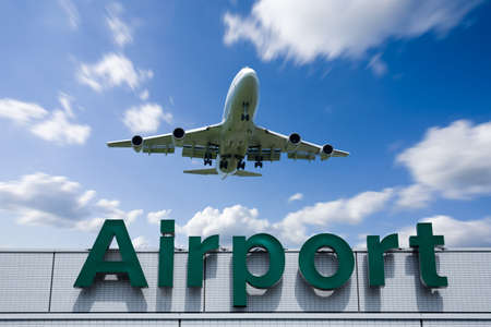 A jetliner aeroplane flying over Airport sign towards