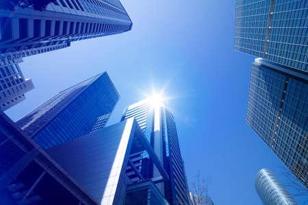 Foto de Looking up at tall skyscrapers against a blue sky in an urban environment - Imagen libre de derechos