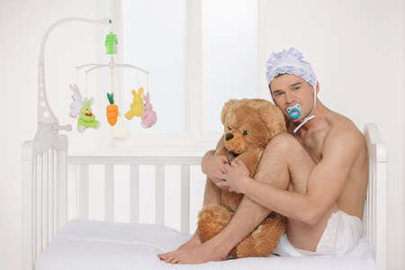 Photo for Big baby. Infant adult man in diaper holding teddy bear while sitting on the baby bed - Royalty Free Image
