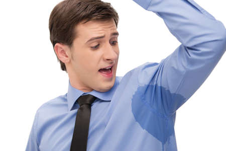 Photo pour Young man is sweating a lot. Looking with surprice at spot on a shirt - image libre de droit