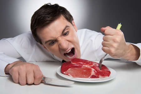 Photo pour Hungry man can not wait till meat is cooked - image libre de droit