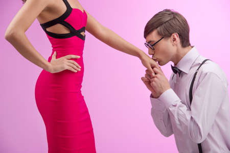 Nerd and beauty. Side view of young nerd man kissing woman hand while standing together against pink background