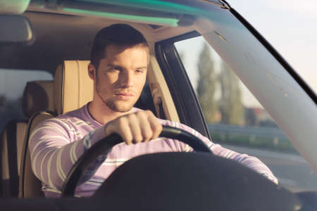 Photo for Handsome young man driving a car holding the right hand on the wheel - Royalty Free Image