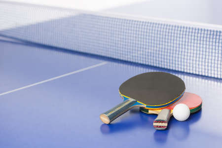 Table tennis rackets. Top view of table tennis rackets and ball lying on the tennis table
