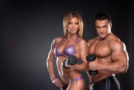 Foto de Couple of well trained bodybuilder with dumbbells. Woman and man standing over black background - Imagen libre de derechos