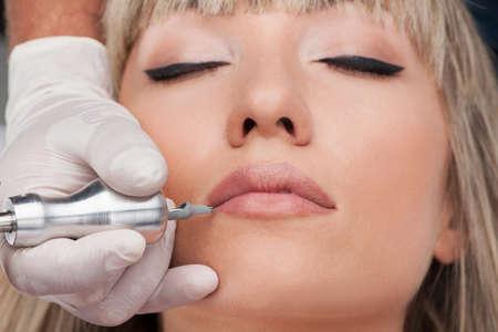 professional tattooist making permanent make up. beautiful woman getting tattoo on face