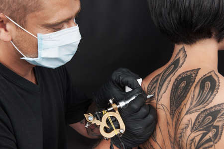 Photo pour professional tattooist making back tattoo. young girl receiving beautiful tattoo - image libre de droit