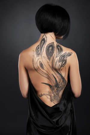 Photo pour beautiful young lady with back tattoo. dark hair girl with tattoo on black background - image libre de droit