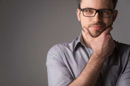 Foto de Close-up portrait of attractive young man holding chin. Man standing on gray background with glasses - Imagen libre de derechos