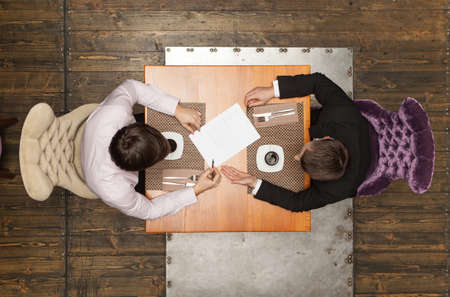 Photo pour two friends sitting in cafe and eating lunch. top view of two colleagues met in restaurant - image libre de droit