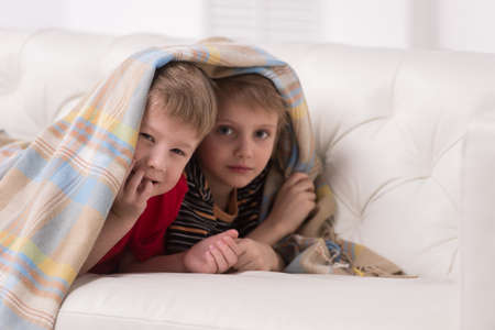 Two children looking into camera under blanket. two friends hiding under coverlet and smiling