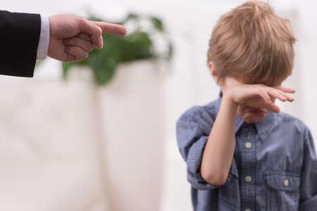 Foto de Strict father discipline naughty son. Isolated on white background boy wiping tears - Imagen libre de derechos