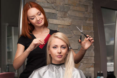 Photo pour Happy young woman getting new haircut by hairdresser at parlor. redhead hairdresser cutting client's hair in beauty salon - image libre de droit