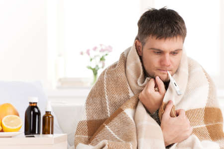 Foto de Man with cold sitting on sofa with thermometer in mouth. Man at home sick with flu, taking his temmperature - Imagen libre de derechos