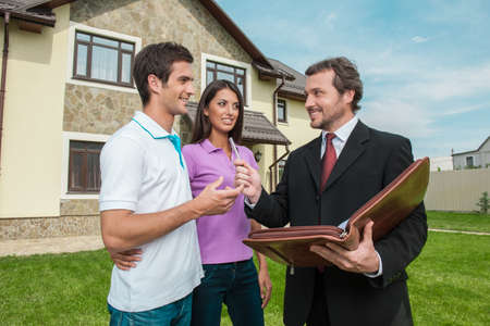 Photo for Young couple signing renting contract with real estate agent. agent giving pen to sign agreement for house sale - Royalty Free Image