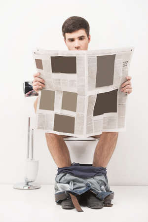 Foto de Young handsome man sitting on toilet and reading magazine. guy reading articles and stories in newspaper while in loo - Imagen libre de derechos