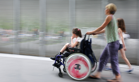 Photo pour abstract image of child with disabilities in a wheelchair, accompanied and modern style with a blurred background - image libre de droit