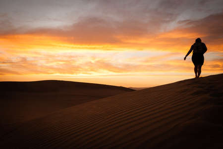 sunset in the desert with a black silhouette of a person hiking