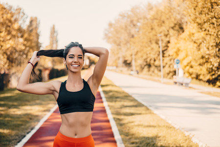 Photo for Woman tying hair in ponytail getting ready for run.  - Royalty Free Image