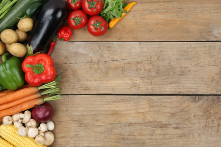 Vegetables like tomatoes, paprika and carrots on a wooden board with copyspace