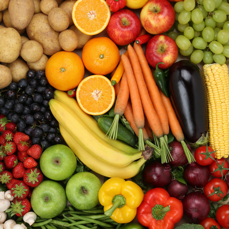 Vegetarian fruits and vegetables like apples, oranges and tomatoes forming a background