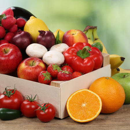 Vegetarian fruits and vegetables like oranges, apples and tomatoes in box