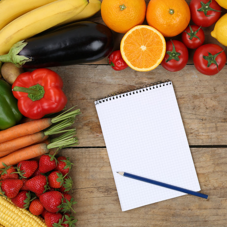Shopping list with fruits and vegetables like oranges, apples and tomatoes on a wooden board