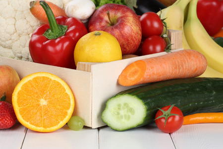 Fruits and vegetables like oranges, apple, tomatoes, banana in wooden box