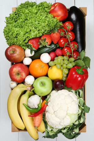 Fruits and vegetables like oranges, apple, tomatoes, banana in wooden box groceries
