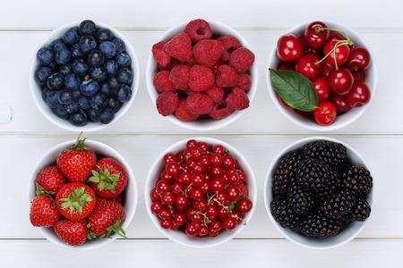 Foto de Berry fruits in bowls with strawberries, blueberries, red currants, cherries, raspberries and blackberries - Imagen libre de derechos