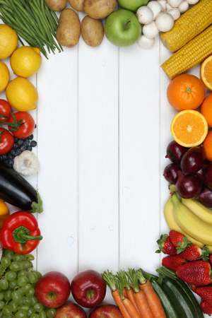 Healthy vegetarian and vegan eating frame from vegetables and fruits like tomato, apple, orange with copyspace