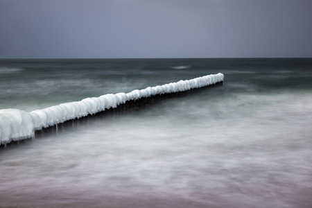 Photo for Frozen breakwaters on the popular beach in Chalupy village near Hel, Poland - Royalty Free Image