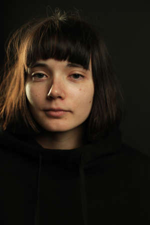 Photo for Portrait of young brunette with short hair and bob haircut, straight bang, without make up, calm expression, wearing black hoodie, looking at camera, isolated on black background, space for text - Royalty Free Image
