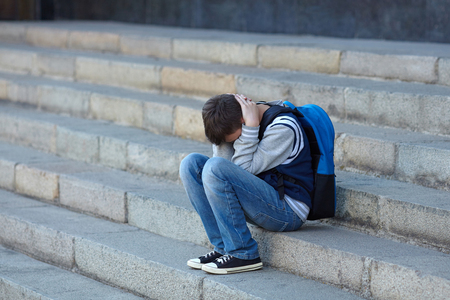 Photo pour Schoolboy crying in the yard of the school. Negative emotion. - image libre de droit