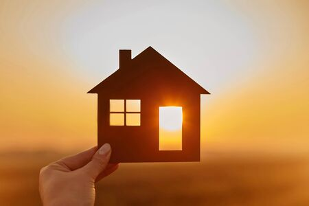 Photo for Woman hand holds wooden house against the sun. Solar energy. Children dreams. International day of families. Home protection insurance concept. Planning to buy property. A symbol for ecology. Affordable housing. Real estate agent offer house. Choose what's the best. - Royalty Free Image