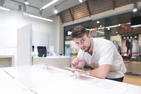 Foto für Handsome man stands next to a showcase with tablet stylus in his hands and looks at the camera. Buyer looks at the tablets in the electronics store. - Lizenzfreies Bild